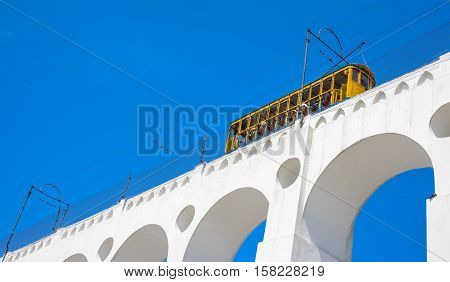 Tram of Santa Tereza, Bonde de Santa Teresa, drives along distinctive white arches, Arcos da Lapa, of the landmark in historic district of Rio de Janeiro - Brazil.