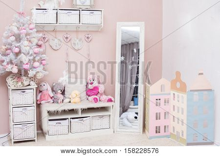 Christmas season in pink color living room with small decorated holiday tree and New Year holiday interior. Horizontal