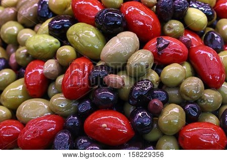 Mix of assorted whole Italian olives (black green red) in oil close up retail market stall display high angle view
