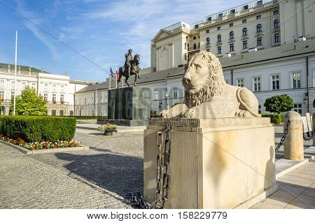 Stone statue of a lion lying in front of the Presidential Palace behind it is a monument to Prince Jozef Poniatowski in Warsaw Poland