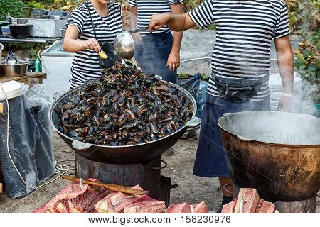 Steamed black sea mussels in cauldron with vegetables. Street food festival