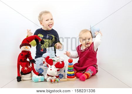 Christmas, Holidays, Children, people concept - happy little boy and little baby girl playing with Christmas presents