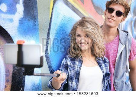 Happy couple taking selfie on street