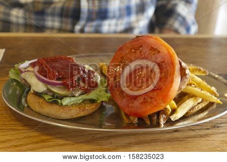 Close up of a greasy all American lunch of a cheeseburger with meat and cheese ketchup French fries lettuce tomato and onion