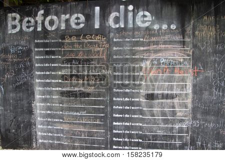 "Asheville North Carolina USA - July 8 2016: Close up of the ""Before I Die"" chalkboard wall where people have written down the things they want to do before they die on July 8 2016 in downtown Asheville North Carolina poster"