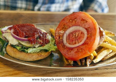 Close up of a greasy all American lunch of a cheeseburger with meat and cheese pickle ketchup French fries lettuce tomato and onion