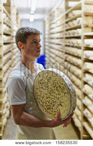 Cheesemaker Holds Wheel Of Comte Cheese At Franche Comte Creamery