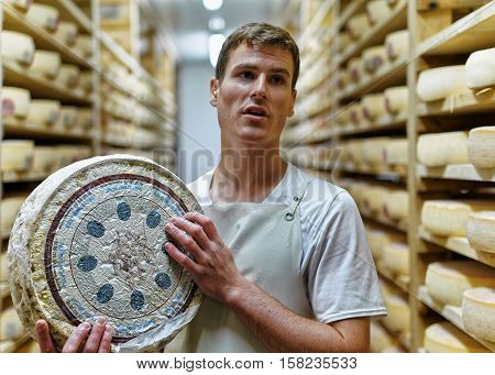 Cheesemaker Holding Wheel Of Comte Cheese At Creamery