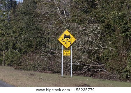 A North Carolina Interstate slippery road sign stands next to downed trees after Hurricane Matthew