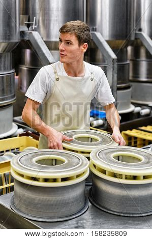 Cheesemaker Putting Young Gruyere Comte Cheese In Forms In Dairy