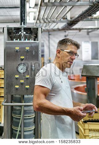 Cheesemaker Working At Gruyere Comte Cheese Dairy