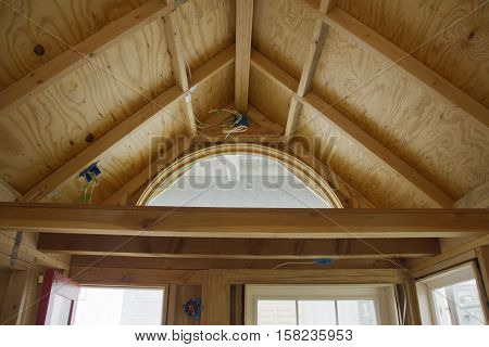 A tiny house storage loft in the process of being built made of wood with windows and exposed electrical wiring