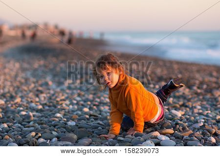 Girl in a sweater dabbles in the autumn beach.
