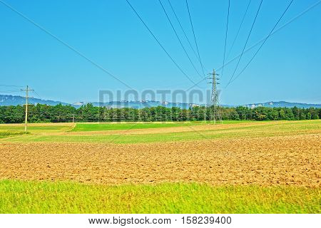 Field and electric transmission lines in a Swiss village in Yverdon les Bains in Jura Nord Vaudois district of Canton Vaud in Switzerland.