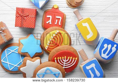 Composition of tasty cookies and dreidels for Hanukkah on light wooden table, closeup
