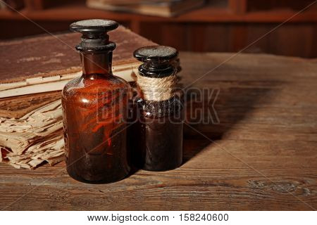 Vintage glass bottles with old books on wooden table, closeup