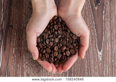 The handful of high-quality coffee beans in hands of a young man