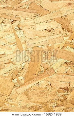 Oriented Strand Board. Wooden panel made from pressed sandy brown wood shavings as background vertical view closeup