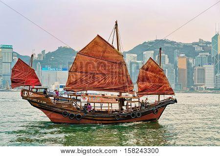 Junk Boat At Victoria Harbor In Hong Kong At Sunset