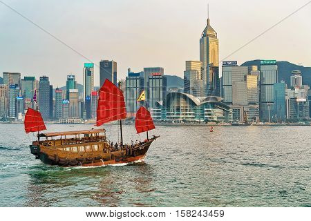 Junk Boat In Victoria Harbor In Hong Kong At Sunset