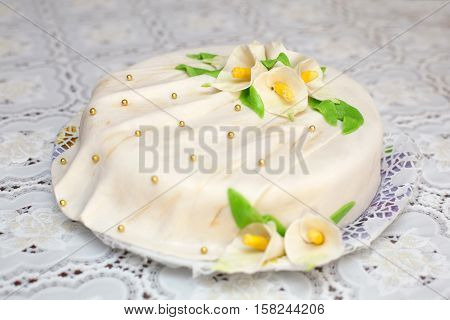 White mastic cake decorated with yellow flowers, closeup