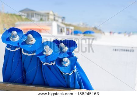Close up view of a group of blue beach umbrellas on a sunny day on Florida's Emerald Coast