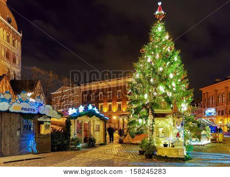 Riga Latvia - December 25 2015: Christmas market in the night at the Dome square in old Riga Latvia. The Dome square is located in the heart of the city. Selective focus. Vintage filter is applied.