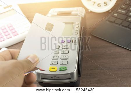 Hand On Hoing Credit Card Terminal Or Edc On Cashier Wooden Table In The Store With Calculator, Cloc