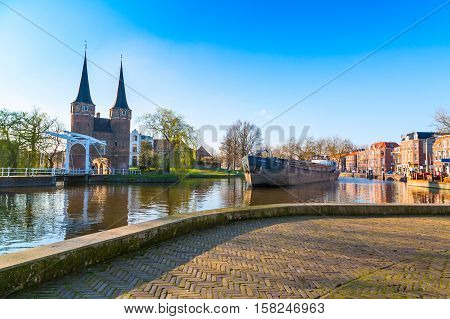 Delft, Netherlands - April 8, 2016: Ship near Oostpoort or Eastern Gate domes, canal and house reflection, Delft, Netherlands, Holland against blue sky