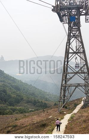Ngong Ping hill and the cable car in Lantau Island in Hong Kong. Man on he background