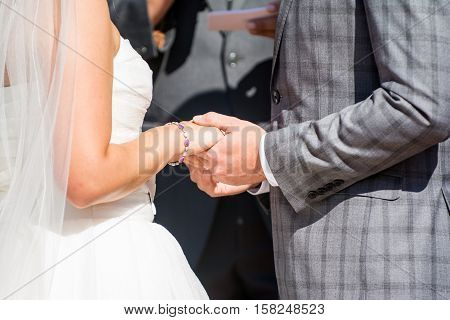 A bride and groom hold hands during the wedding ceremony
