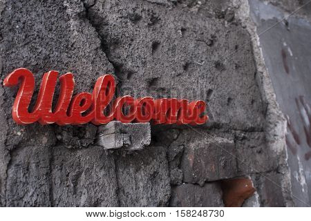 wooden welcome sign on old brick wall