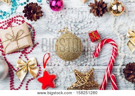 Craft gift, Christmas balls, cones, candy cane and New Year decorations on grey wooden background, top view