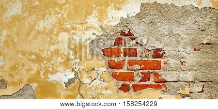 Grunge Brickwall With Broken Stucco Texture. Old Brick Wall With Damaged Shabby Yellow Plaster Layer Background. Lime Wash Distressed Stonewall Chipped Rough Stonewall Uneven Web Banner