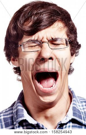 Face close up of young hispanic man wearing glasses and blue shirt yawning over white background - fatigue concept