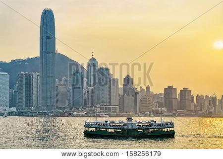 Star Ferry At Victoria Harbor And Hong Kong Skyline At Sundown