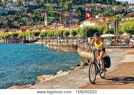 Ascona Switzerland - August 23 2016: Woman riding a bicycle at the promenade at the luxurious resort in Ascona on Lake Maggiore in Ticino canton in Switzerland.