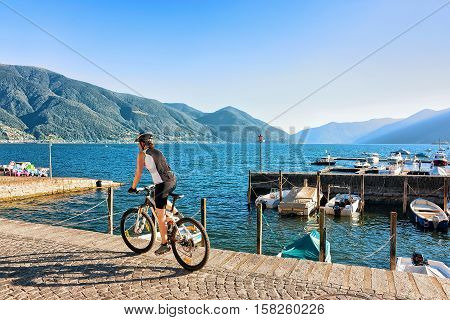 Woman riding a bicycle at the promenade at the luxurious resort in Ascona on Lake Maggiore Ticino canton in Switzerland.