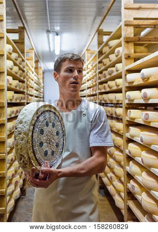 Worker Holding A Wheel Of Cheese At Franche Comte Creamery