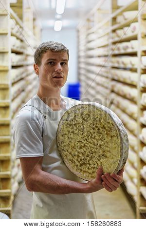 Worker Holding Wheel Of Comte Cheese At Franche Comte Creamery