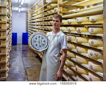 Worker Holds A Wheel Of Cheese At Franche Comte Creamery