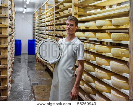 Worker Holds A Wheel Of Cheese In Franche Comte Creamery