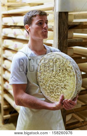 Worker Holds Wheel Of Comte Cheese At Creamery