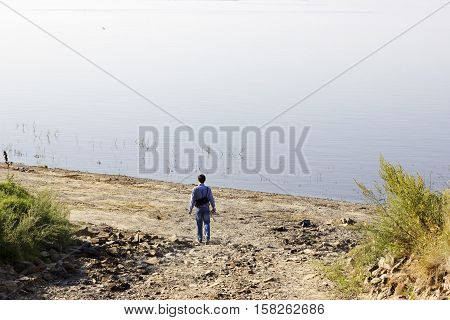 Man admires the nature. Small human stays before huge lake on the stone beach. Still endless water before photographer