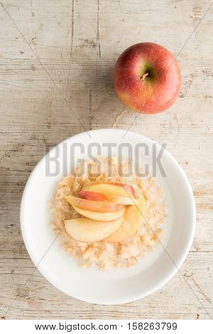 Bowl Of Oatmeal And Apple Slices On Wooden Background