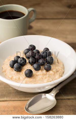 Breakfast Porridge, Blueberry Oatmeal And Coffee On Wooden Background