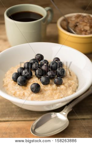 Blueberry Topped Oatmeal And Coffee On Wooden Background
