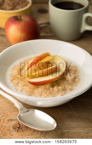 Bowl Of Oatmeal And Sliced Apples On Wooden Background