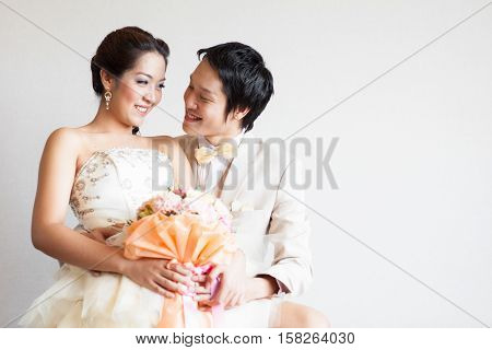 Portrait of young elegant enamoured just married groom and bride embracing at Wedding