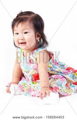 Cute baby girl sitting in studio on white board.